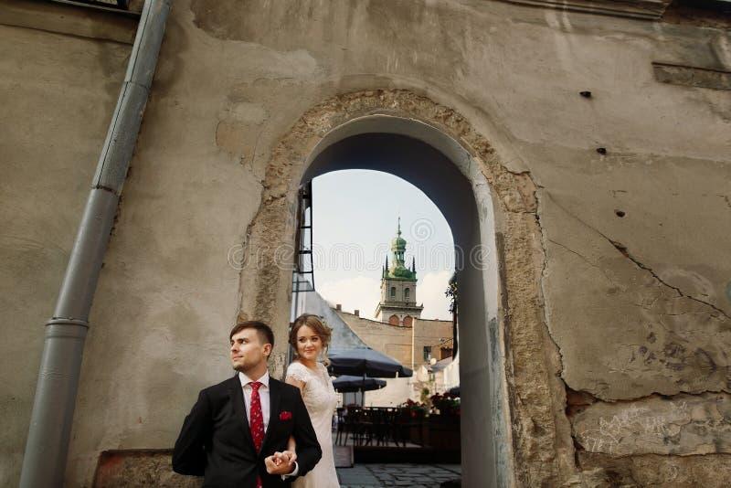 Romantyczna para nowożeńcy trzyma ręki zbliża starego budynek wal zdjęcia royalty free