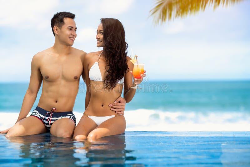 Romantyczna para relaksuje blisko pływackiego basenu zdjęcia royalty free