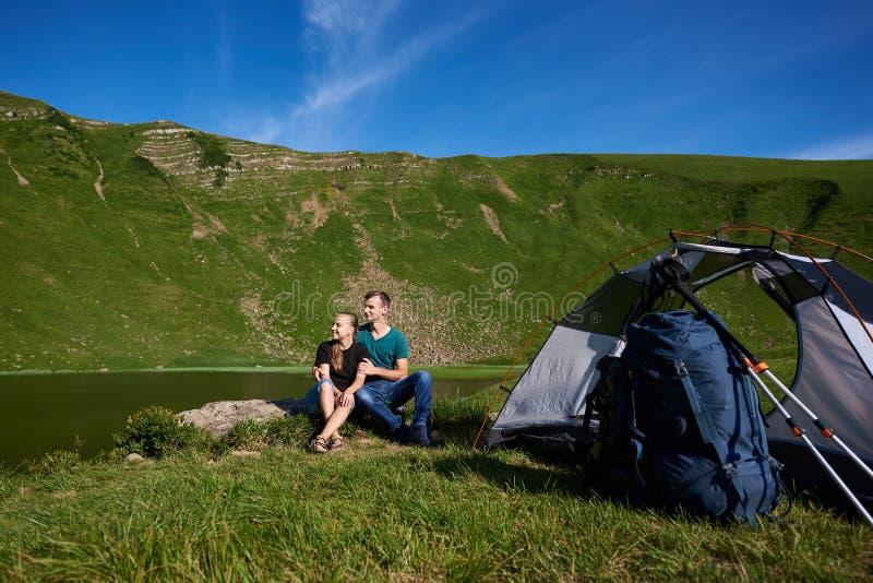 Romantyczna para siedzi na rockowym pobliskim namiocie, plecak i trekking wtykamy przeciw górom i jezioru zdjęcia royalty free