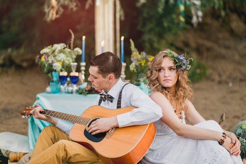Romantyczna para siedzi outdoors przy zmierzchem z mężczyzna bawić się obrazy stock