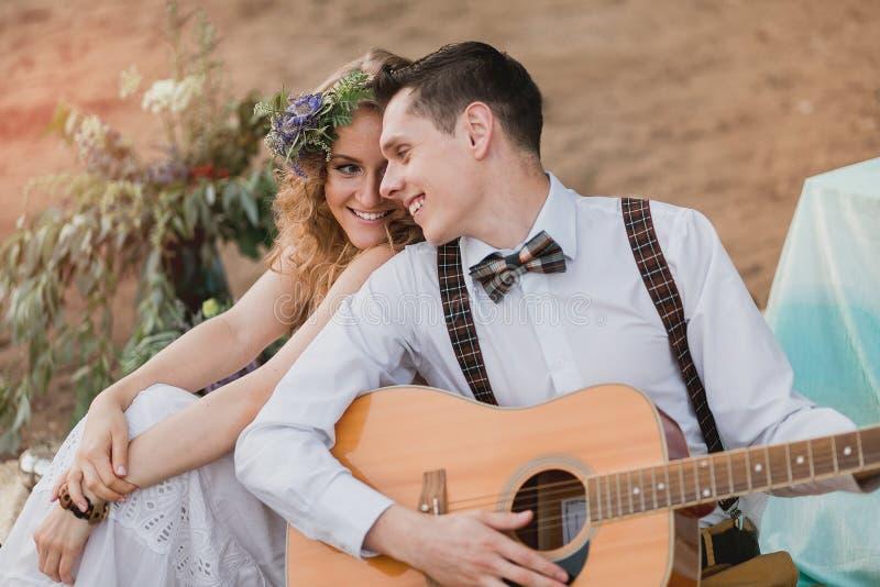 Romantyczna para siedzi outdoors przy zmierzchem z mężczyzna bawić się gitarę zdjęcia royalty free