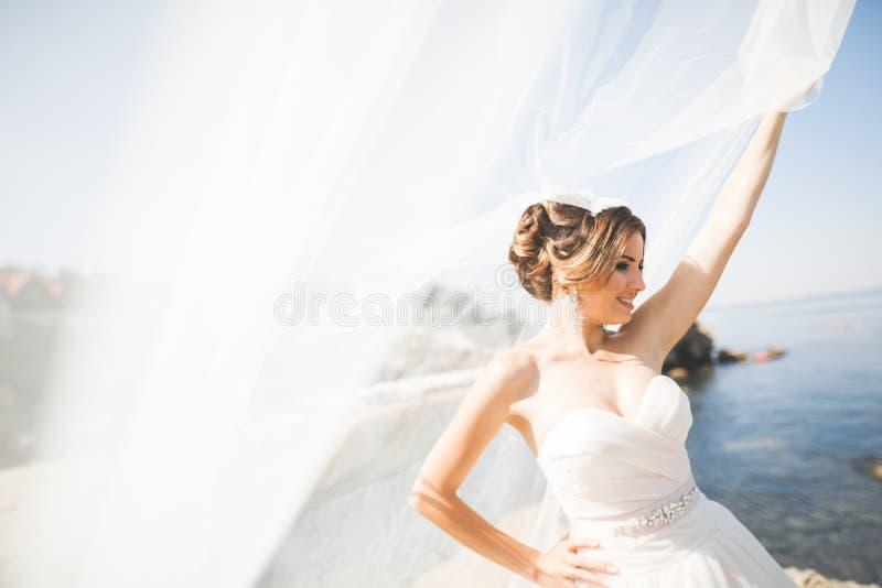 Romantyczna piękna panna młoda w bielu smokingowy pozować na tła morzu fotografia stock