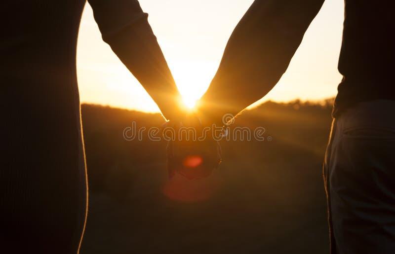 Romantyczne pary mienia ręki i dopatrywanie piękny zmierzch obrazy stock