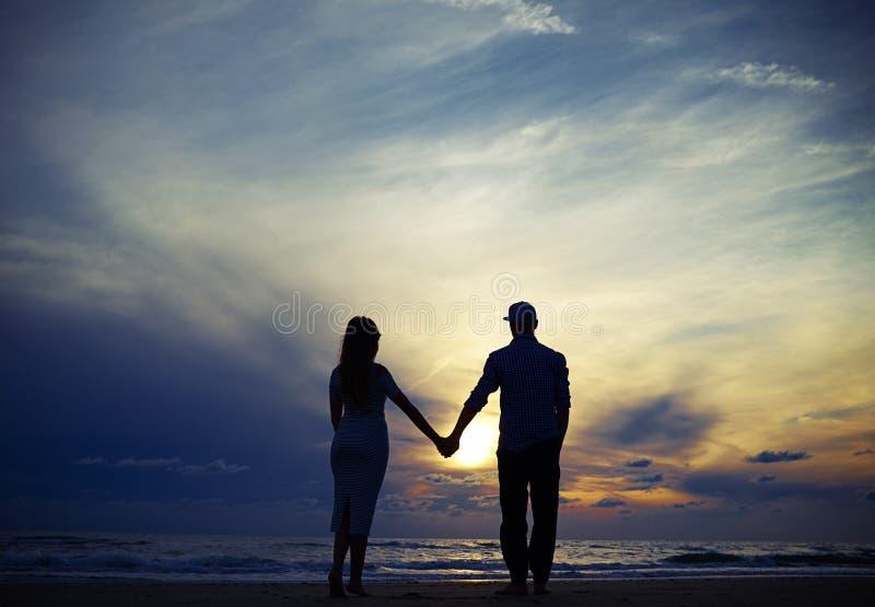 Romantyczne pary mienia ręki podczas gdy patrzejący zmierzch obraz royalty free