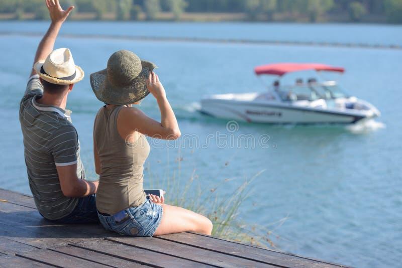 Romantyczni potomstwa dobierają się obsiadanie na molu cieszy się pięknego jezioro zdjęcie royalty free