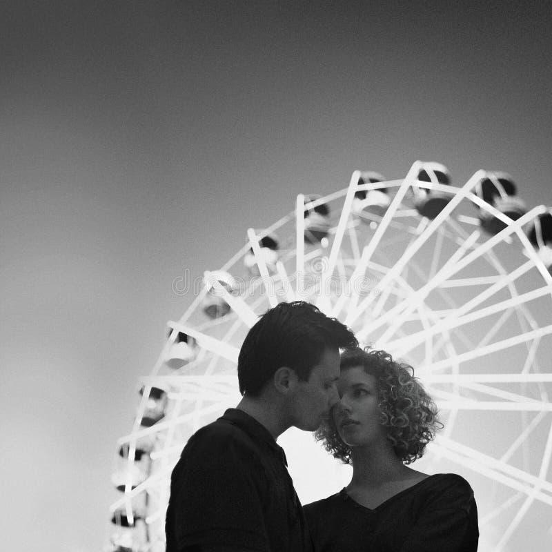 Romantyczni potomstwa dobierają się przed Ferris toczą wewnątrz parka rozrywki Chłopiec i kędzierzawa dziewczyna tenderly obejmuj obraz stock