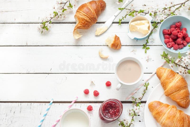 Romantyczny francuz lub wiejski śniadanie z croissants, dżemem i malinkami na bielu, zdjęcia stock