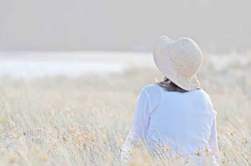 Romantyczny kobiety obsiadanie w wysokiej długiej trawie zdjęcie royalty free