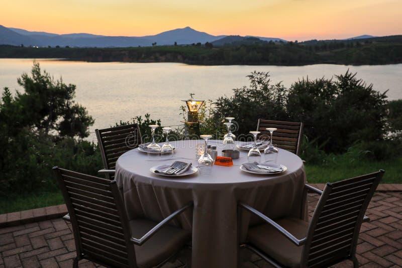 Romantyczny lato wieczór w restauraci - stół słuzyć dla cztery persons z zmierzchu widokiem przy jeziornym maratonem, Grecja obrazy royalty free