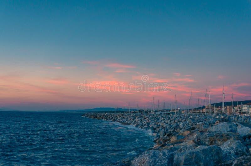 Romantyczny nabrzeżny zmierzchu seascape z niebieskim niebem i jaskrawymi różowymi chmurami zdjęcie royalty free
