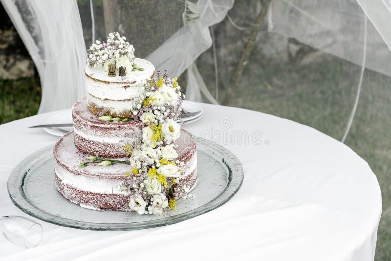Romantyczny nieociosany kwiecistego projekta ślubny tort na stole outdoors obrazy stock