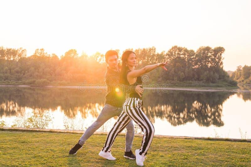 Romantyczny, ogólnospołeczny taniec, i ludzie pojęć - potomstwa dobierają się dancingowego bachata na tle zmierzch zdjęcie royalty free