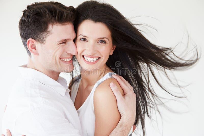 Romantyczny pary obejmowanie Przeciw Białemu Pracownianemu tłu obrazy royalty free