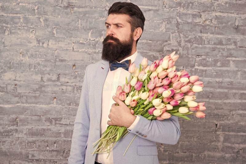 Romantyczny prezent Macho dostaje gotowa romantyczna data Tulipany dla Ona Obs?uguje dobrze przygotowywaj?cego smokingu ??ku kraw zdjęcia royalty free