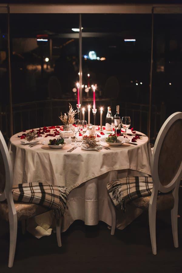 Romantyczny stołowy położenie z winem, pięknymi kwiatami w pudełku, pustymi szkłami, różanymi płatkami i świeczkami, obrazy royalty free