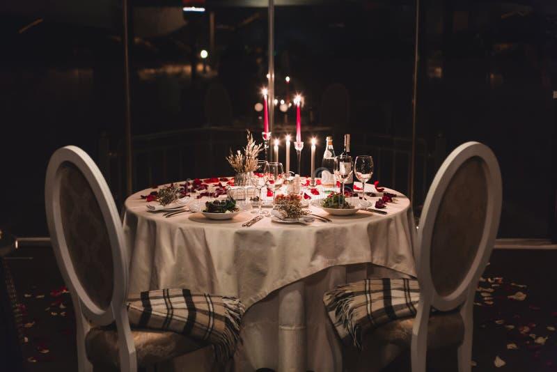Romantyczny stołowy położenie z winem, pięknymi kwiatami w pudełku, pustymi szkłami, różanymi płatkami i świeczkami, fotografia royalty free