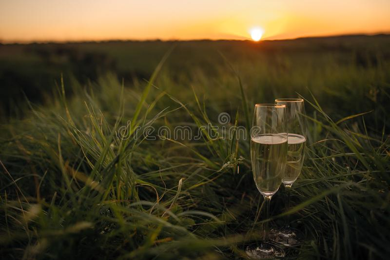 Romantyczny szkło wina obsiadanie na plaży przy kolorowymi zmierzchów szkłami biały wino przeciw zmierzchowi obrazy stock