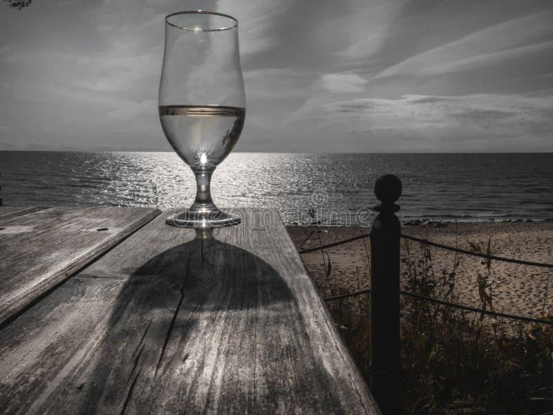 Romantyczny wieczór zmierzch z mglistym szkłem biały wino na tła morzu na drewnianym stole, fotografia stock
