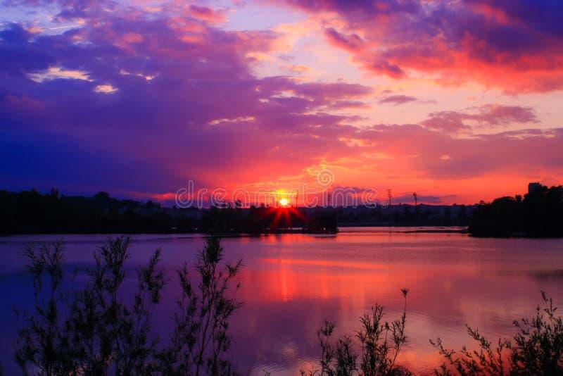 Romantyczny zmierzch nad jeziorem z odbiciami słońce i fotografia royalty free