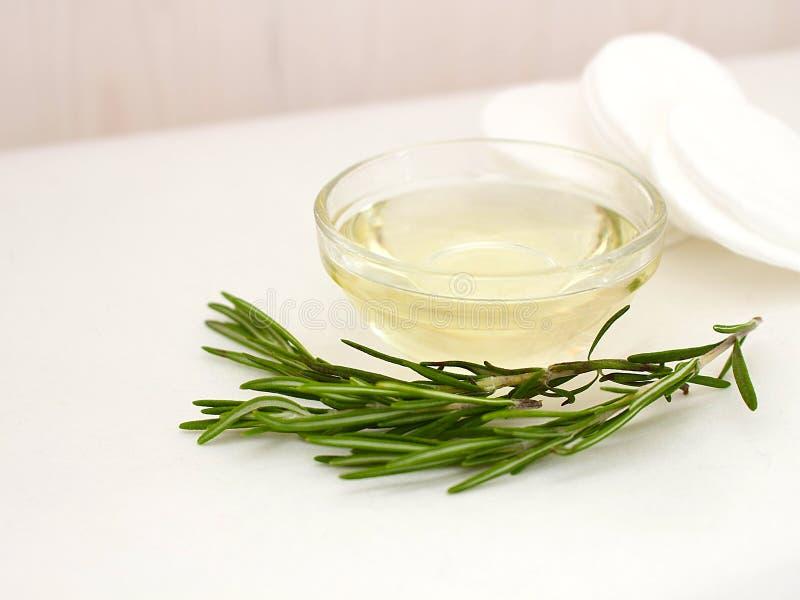 Romarin naturel parfumé dans un bol en verre avec une branche de romarin et des protections de coton contre un mur en bois blanc images stock