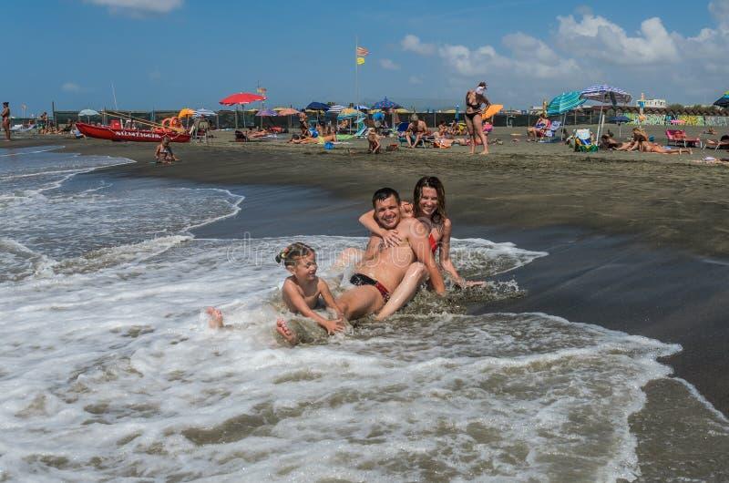 ROME, ITALIË - AUGUSTUS 2018: Het jonge gelukkige de de familiemamma, papa en dochter spelen en baden in het overzees tijdens de  royalty-vrije stock foto's