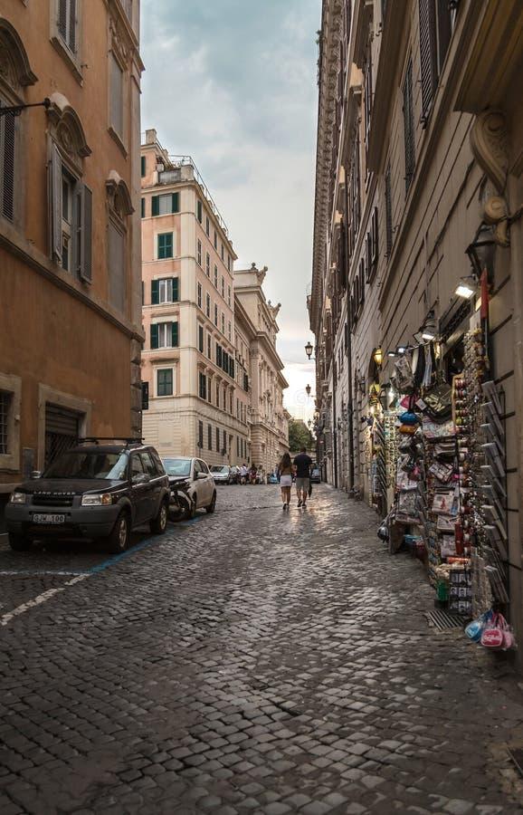 Rome, Italië - Augustus 20, 2018: Typische oude Roman smalle straat Oude huizen met giftwinkels op de achtergrond van de avondhem stock afbeelding