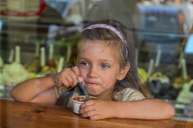 ROME, ITALIË - AUGUSTUS 2018: Weinig charmant babymeisje die roomijs in een koffie, mening door het venster eten stock foto
