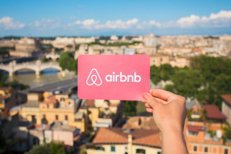 Rome, Italië - Mei 13, 2018: Het embleem van Airbnb van de persoonsholding ter beschikking met stad op achtergrond royalty-vrije stock afbeeldingen