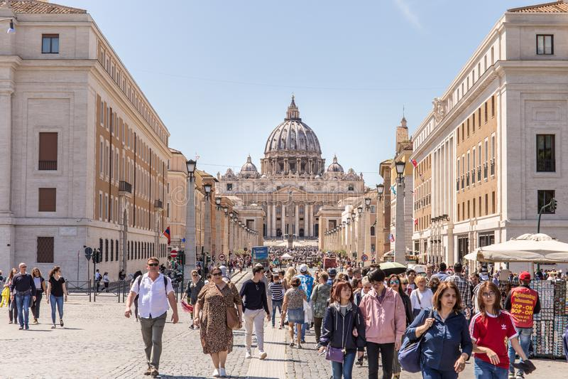 ROME ITALIEN - APRIL 27, 2019: Folk som promenerar det berömt via dellaen Conciliazione med Stets Peter basilika royaltyfria foton