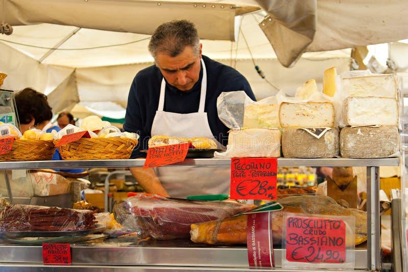 ROME ITALIEN - APRILE, 6: Säljare av ost och prosciuttoen på den marknadsCampo deien Fiori, Aprile 6, 2013 arkivfoton