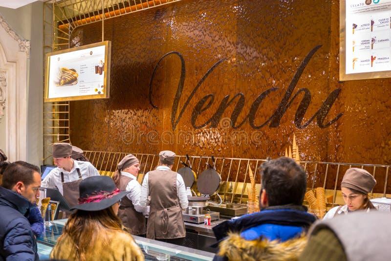 Rome Italien - Januari 11, 2019: Folket i den Venchi sötsaken shoppar med flödande choklad på väggen, Rome Venchi är en italienar arkivbild