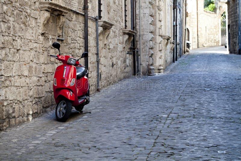 Rome Italien - mars 31, 2019: Röd sparkcykelVespa som parkeras på den gamla gatan royaltyfri bild