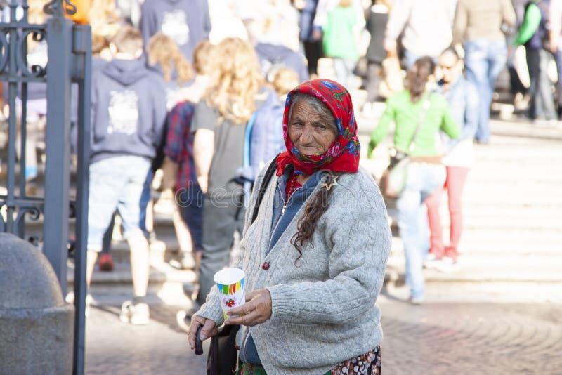 Rome Italien, Oktober 9, 2011: Äldre kvinna som frågar för allmosa på ingången till en katolsk kyrka arkivbild