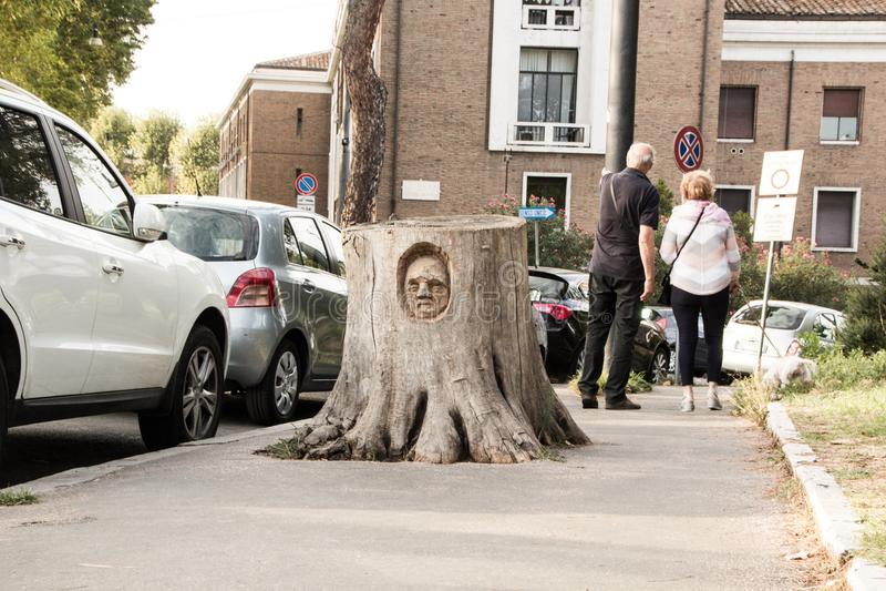 Rome Italien - September 13, 2017: Framsidan sned in i en stubbe Skulptören Andrea Gandini snider framsidor i träden för snittet  arkivfoto