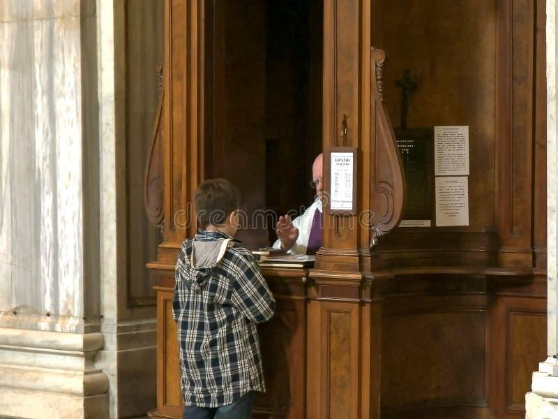 ROME ITALIEN SEPTEMBER 30, 2015: pojke som utför katolsk bikt på den basilikaSanta Maria maggioren, rome arkivbild