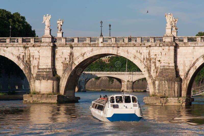Rome Italien, turist- fartyg på den Tiber floden, med gamla broar, i solnedgången royaltyfri foto
