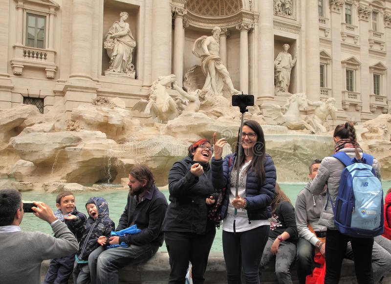 ROME, ITALY - APRIL 9, 2016: Crowd of tourists visiting and posing in the front of the Trevi fountain (Fontana di Trevi), one. Of the major sights of Rome royalty free stock image