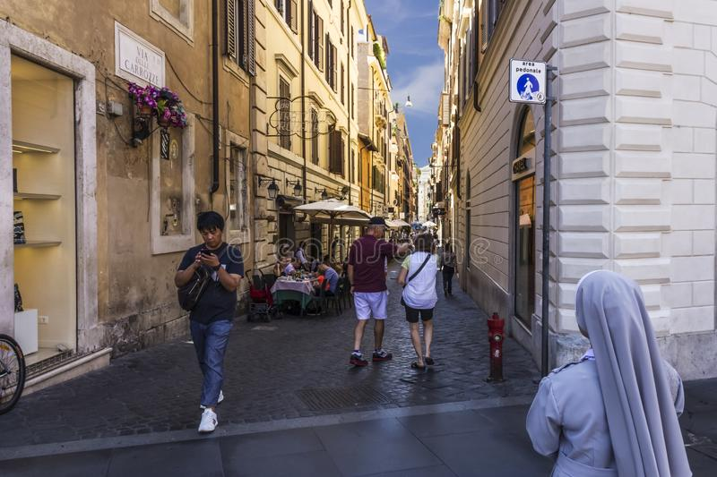 Rome/Italy - August 26, 2018: Italian Street Via Delle Carrozze with tourists, street cafes and a votaress royalty free stock photography