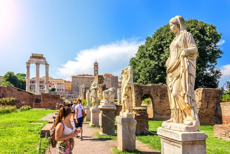 Tourists watching each other and the Statues of virgins near the House of the Vestals, Roman Forum. Rome/Italy - August 24, 2018: Tourists watching each other royalty free stock photo