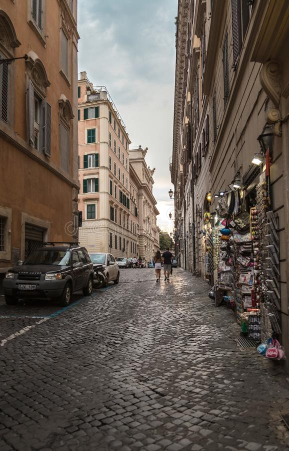 Rome, Italy - August 20, 2018: Typical old Roman narrow street. Ancient houses with gift shops on evening sky background. stock image