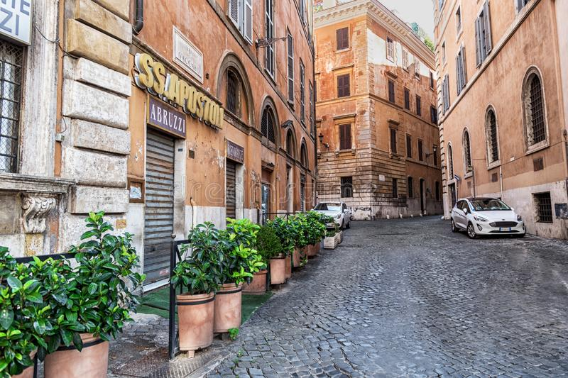 Rome, Italy - August 22, 2018: Typical old Roman narrow street. Green plants in front of small restaurant windows. Cars parked near old houses on paving stones stock photos