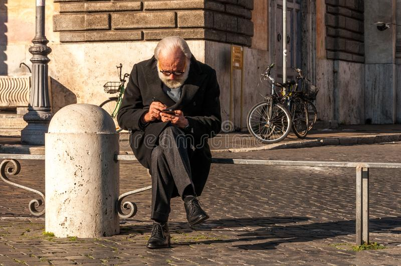Rome, Italy - Dec 25, 2017 - Old man sitting on the barrier in t stock photography