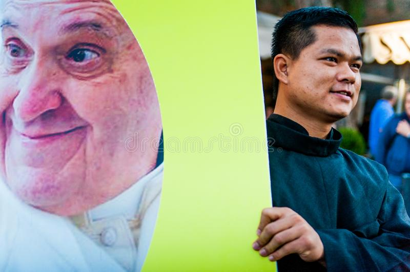 Rome, Italy - 20 january 2019: a young asiatic priest carry a big banner with an image of pope francis during a cathilic march in stock image