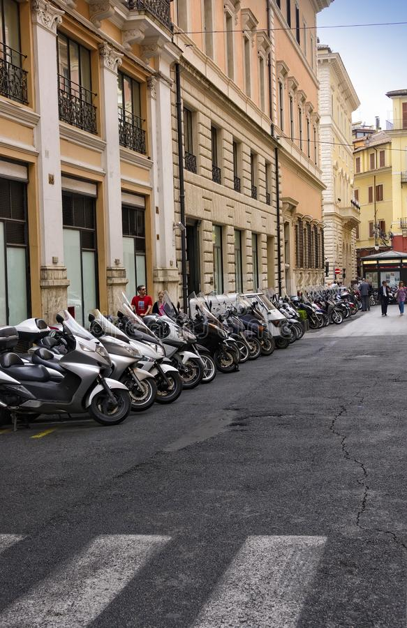 Narrow alleyway in Rome, Italy. Rome, Italy -June 10, 2016:  Numerous scooters lined up on a small roadway in Rome, Italy royalty free stock image