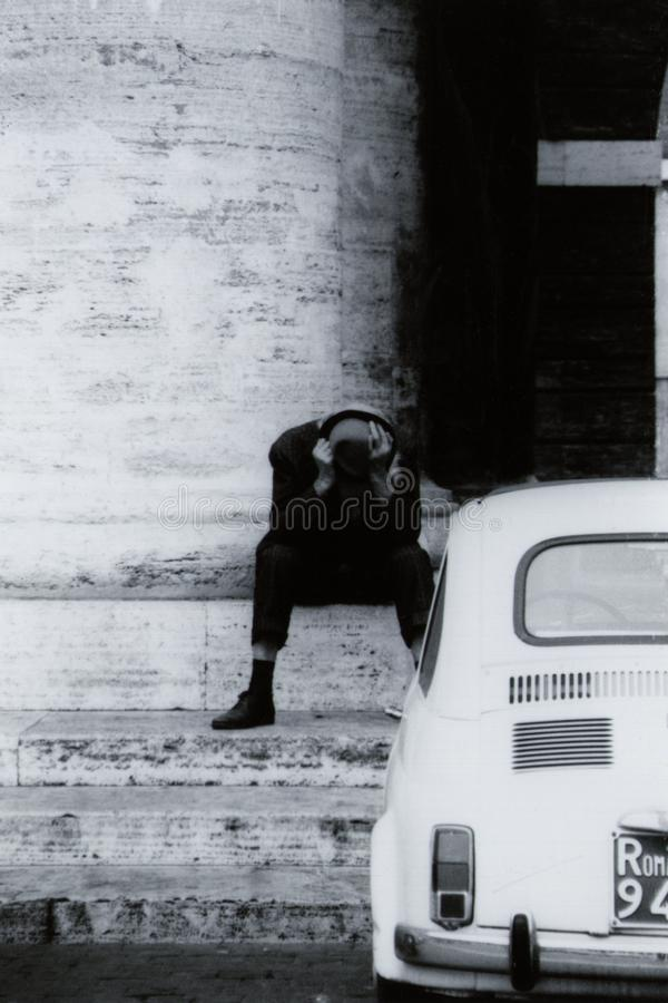 ROME, ITALY, 1970 - A man hides his emotions behind his hat at the foot of a column in St. Peter`s Square stock photo