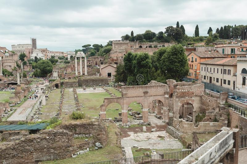 People walk by ancient ruins in antique Roman Forum royalty free stock images