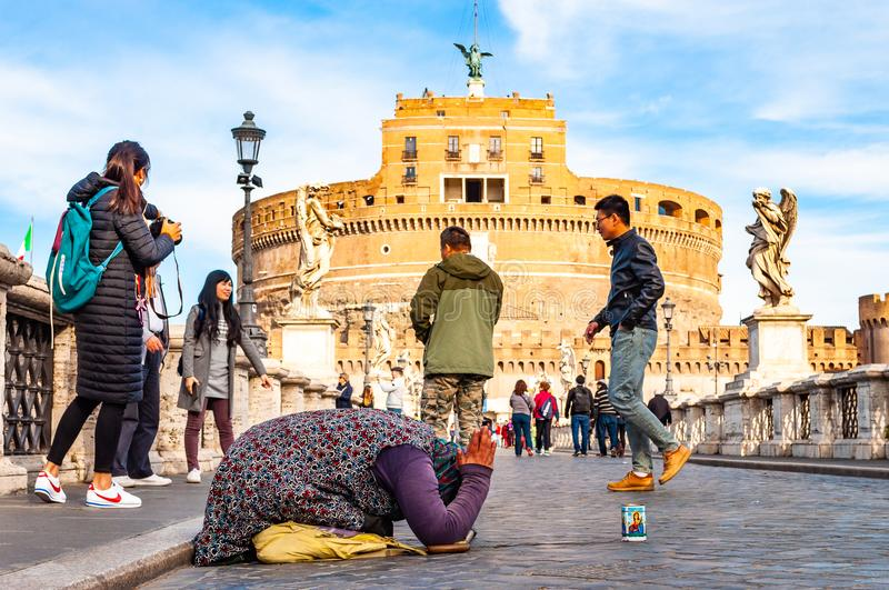 Beggar woman asking alms on her knees on Ponte Sant `Angelo, Bridge of Hadrian full of walking people with Castel Sant `Angelo, royalty free stock photos