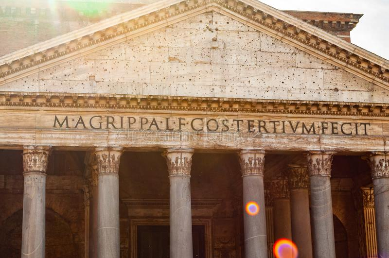 Close-up fragment of the facade of the famous Pantheon temple of all the gods is a former Roman temple with bright sun rays stock photography