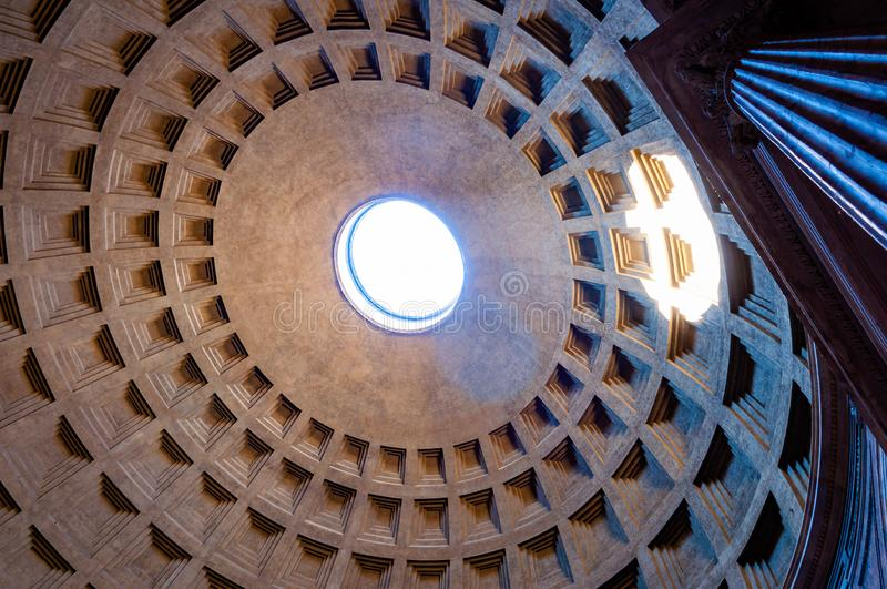 The famous cassette ceiling dome of Pantheon temple of all the gods with wide open rotunda on the top. Sunlight rays penetrating. Rome, Italy - November 18, 2018 stock photos