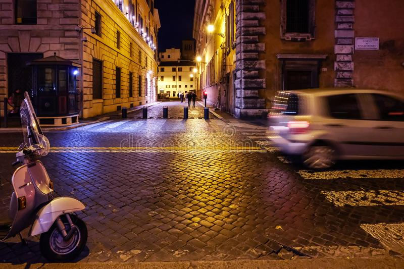 Vespa bike and passing cars in central Rome. Night scene royalty free stock photo